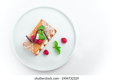 Mille feuille dessert with raspberry and whipped sour cream on a white plate, isolated on white