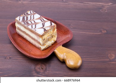 Mille feuille Napoleon french custard pastry on a cashew fruit format massaranduba wood dish on an ipe wood table