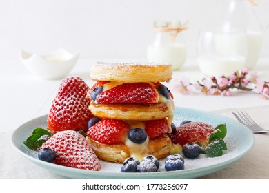 Mille Feuille, puff pastry discs with giant strawberries and blueberries with lemon curd. Gordon Ramsay recipe. Delicious French dessert with summer berries.