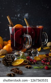 milled Hot wine with Christmas decorations background. Holiday dark photo.  citrus, cinnamon sticks, anise stars, red berries