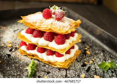 Millefeuille dessert with raspberry on black background
