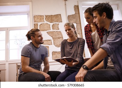 Millenial business team sitting and standing around in a semi circle all looking thoughtfully at the tablet in an interesting discussion