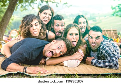Millenial friends taking selfie with funny faces at pic nic barbecue - Happy youth friendship concept with millennial young people having fun together with tongue out -  Bright green azure filter