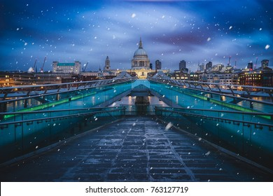Millenium bridge on a cold winter morning with falling snow, London, United Kingdom