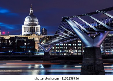 The Millenium bridge over the Thames rivver in London at night. The St Paul's cathedral can be seen on the background illuminated.