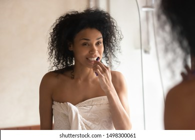 Millennial african American woman in shower towel look in mirror clean brush tooth in bathroom, young biracial female perform morning face care routine, do cleanup oral hygiene, use toothbrush