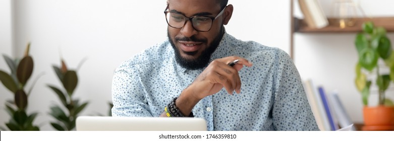Millennial African employee sit at office desk using pc look at screen read e-mail, received good business news, entrepreneur do remote job from home, horizontal photo banner for website header design