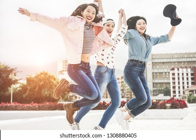 Millennial asian women jumping outdoor - Happy girls friends having fun around the city - Generation z, youth, young people lifestyle concept - Focus on center female face