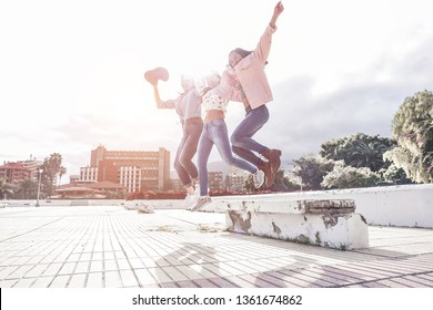 Millennial asian women jumping outdoor - Happy girls friends having fun in urban city park - Generation z, youth, young people lifestyle concept - Focus on right female body