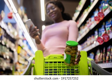 Millennial black lady checking shopping list in mobile app, putting jar of olives into her cart at mall, selective focus. Low angle view. Positive young lady buying foodstuff at mall