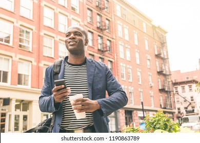 Millennial black man portrait in New York. Young man with paper cup and mobile phone in the city with buildings on background. Commuting to work and lifestyle concepts