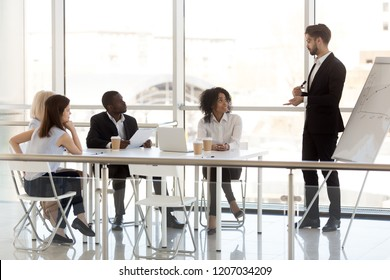 Millennial businessman make flipchart presentation training diverse employees during office meeting, male coach mentoring or training company interns at business briefing, presenting business plan