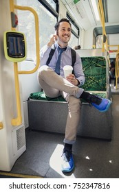 Millennial businessman is talking on the phone and holding a cup of coffee while commuting on the tram in Melbourne, Victoria.