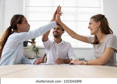 Millennial businesspeople sitting at desk in office room feel gratification from solving business issues reached corporate goals. Successful employees giving high hive showing respect and team spirit
