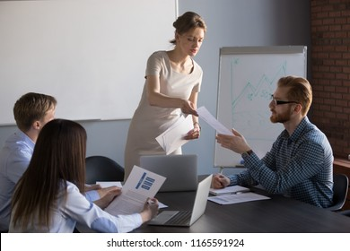 Millennial businesswoman give handout materials to work team members during flipchart presentation, female speaker or coach share documents to workers, presenter hand papers to consider or analyze