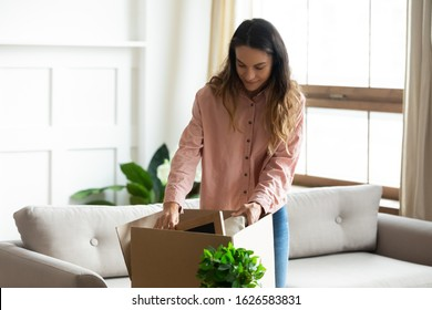 Millennial Caucasian wife unpack cardboard boxed moving to new house or apartment, excited young woman open carton parcel package in living room settle at own home, relocation, ownership concept