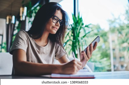 Millennial caucasian woman reading news from social networks using mobile phone at cafe, female blogger making online research on smartphone while creating article for share writing in notepad