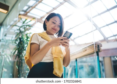 Millennial Chinese woman with cute smile on face checking received email messages via cellphone device, happy Asian female enjoying technology phoning during cell texting with blog followers