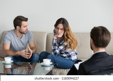 Millennial couple discuss family problems sitting on couch at counselor or psychologist, male relationship expert help husband and wife, saving marriage or overcoming difficulties at therapy session