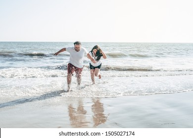 A millennial couple running and splashing water on the beach in California. Wearing summer clothing getting wet. Both are smiling and having fun. The male almost falls.