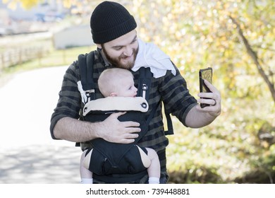 Millennial Dad with Baby in Carrier Outside Walking & Taking Selfies with Phone on a Beautiful Fall Day