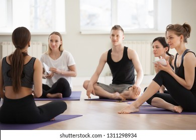 Millennial diverse people sit in circle at yoga workshop, write in notebooks listening to teacher or trainer, sporty men and women study at seminar at gym or training studio, becoming future coach