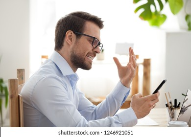 Millennial employee irritated looking at smartphone having app problems, angry male worker holding cellphone annoyed by gadget breakdown, mad man experience mobile trouble or malfunction