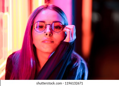 Millennial enigmatic pretty girl with unusual dyed hairstyle near glowing neon wall at night. Blue hair, golden sequins as freckles,nose piercing. Mysterious hipster teenager in glasses.