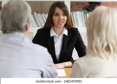 Millennial female bank specialist talk meeting with mature clients or customers help with loan or mortgage, woman relator speak discuss house purchase with pensioners, elderly loyalty program concept