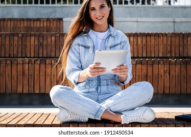 Millennial female in denim sits on park bench holding smart tablet. Woman uses tablet to shop on Internet, sits on street. Woman enjoying social media chat. Student looking at camera, sunny weather