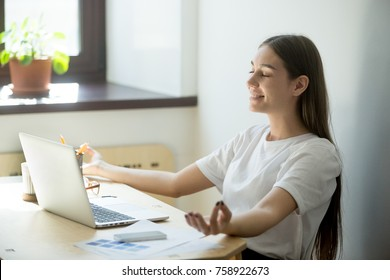 Millennial female designer practicing yoga meditation. Smiling business lady resting in yoga posture on working break. Health  and wellness, stress relief concept