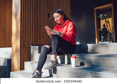 Millennial female making online banking while ticketing at online web service connected to 4g wireless for browsing websites on modern smartphone gadget, concept of millennial generation and mobility