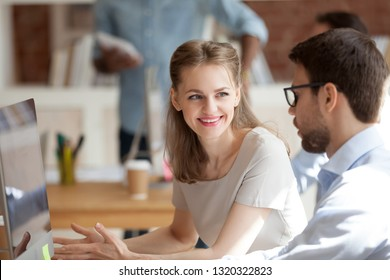 Millennial female and male sitting at coworking area talking working on new project brainstorming together, attractive woman employee has pleasant conversation with colleague or mentor teach trainee