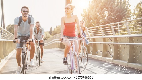 Millennial friends going with bicycles on  city park - Young people having fun in sunny day after univerity - Youth, friendship and healthy lifestyle concept - Focus on center girl face