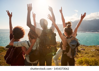 Millennial friends on a hiking trip celebrate reaching the summit and admire the view, back view