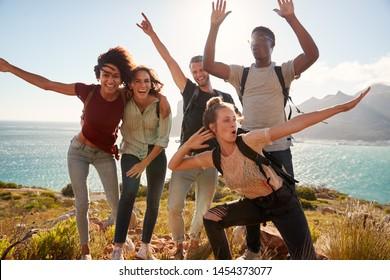Amigos milenarios en un viaje de excursión celebran llegar a la cumbre y se divierten posando para fotos