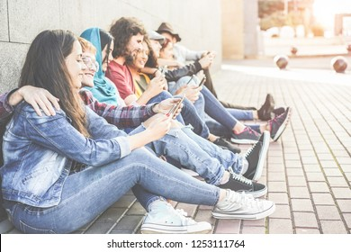 Millennial friends using smartphones sitting outdoor - Diverse culture people addiction to new technology trends - Concept of youth, social lifestyle and friendship - Focus on close-up girl face