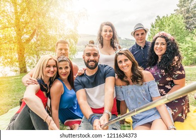 millennial generation friends take a group photo with a selfie stick during an outdoor party in summer. yellow backlight from the left flares into the image. fun lifestyle people concept