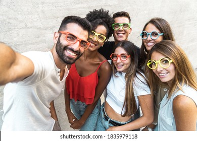 Millennial generation people group taking selfie with mobile phone wearing funny plastic glasses. Young people having fun together taking picture lifestyle concept