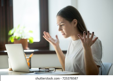 Millennial generation young adult woman looking in laptop computer, fling arms up.  She just found mistake in last assignment, error in contract, disagreement in email or dissatisfied buyer message.