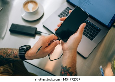 Millennial or generation z young entrepreneur, social media content creator, designer or photographer attaches smartphone to external power bank with charge cable at coworking space