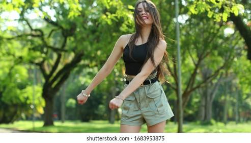 Millennial girl dancing floss dance in outdoor park