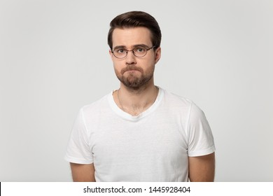 Millennial guy wearing glasses feels upset frustrated or offended with pursed lips posing isolated on gray studio background, lack of self-esteem, guilty made mistake, nervous tension, mess up concept