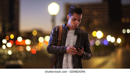 Millennial Hispanic man standing on city bridge at night looking at smartphone