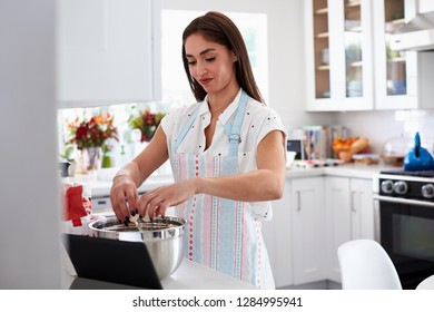 Millennial Hispanic woman breaking egg into cake mixture, following a recipe on her tablet computer