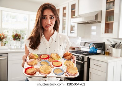 Millennial Hispanic woman presenting her cakes to camera after a baking disaster, close up