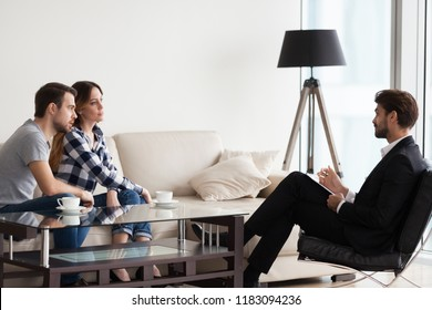 Millennial husband and wife consulting with male psychologist or counselor talking about family problems during therapy session, young couple counseling with relationships expert, saving marriage