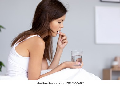 Millennial ill sick woman taking painkiller medicine to relieve headache pain sit on bed in the morning, young girl holding sleeping abortion pill and glass of water suffering from chronic insomnia