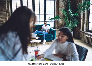 Millennial male blogger connecting to 4g wireless internet for browsing web content while blurred female on frontage discussing ideas, hipster guy using modern technology for online messaging