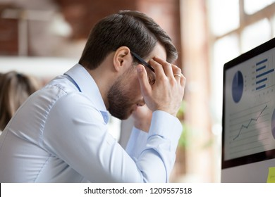 Millennial male employee sit in front of pc with eyes closed, suffering from severe headache, man worker feel unwell at workplace having strong migraine or high blood pressure. Health problem concept